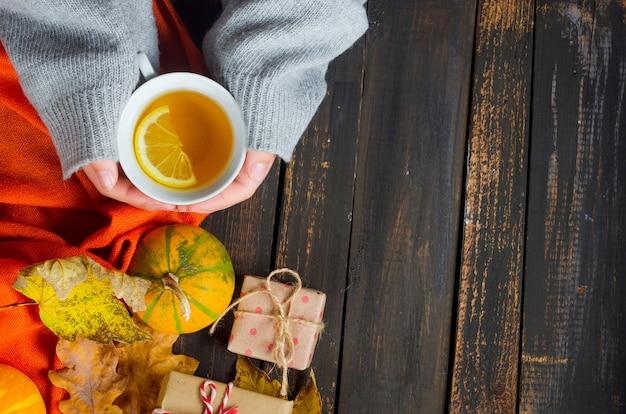 Mani femminili che tengono una tazza di tè al limone sul tavolo scuro di legno con foglie d'autunno, zucche. arredamento autunnale, atmosfera autunnale, natura morta autunnale. concetto di stagione autunnale. distesi, copia spazio