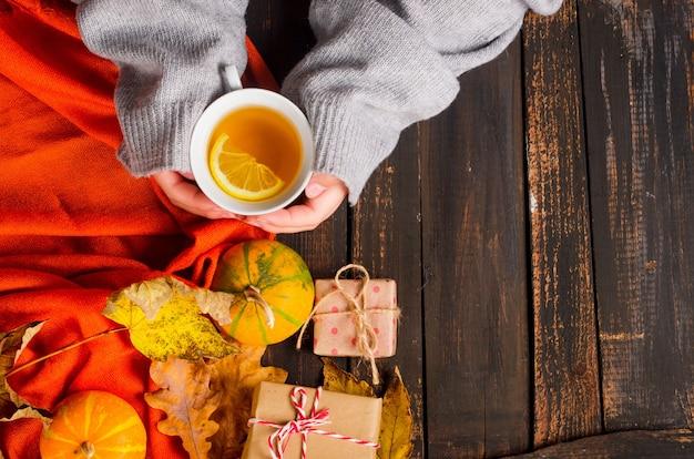 Mani femminili che tengono tazza di tè al limone sulla tavola di legno con foglie di autunno, zucche