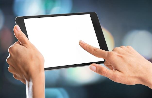 Mani femminili che tengono tablet digitale con schermo bianco su sfondo sfocato