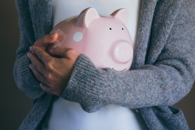 Mani femminili che tengono salvadanaio vuoto close up donna che schiaccia la scatola dell'usato problemi finanziari