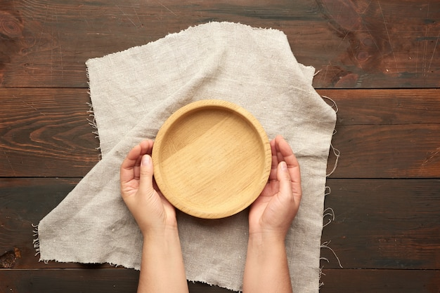 Mani femminili che tengono piatto di legno marrone rotondo vuoto sul tavolo