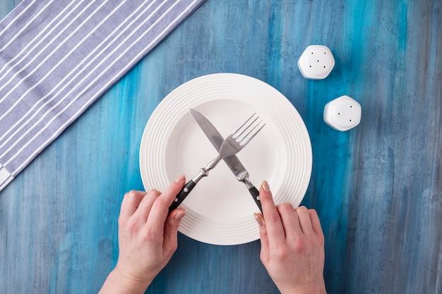 Mani femminili che tengono forchetta e coltello sul piatto bianco
