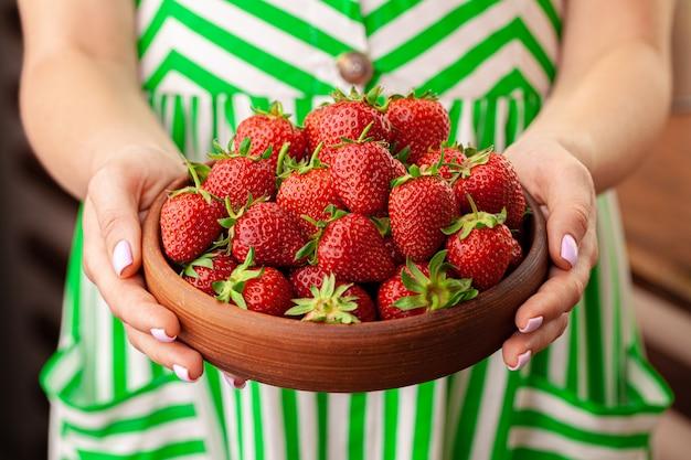 Le mani femminili che tengono le fragole fresche si chiudono su. concetto di estate.