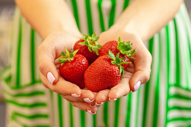 Le mani femminili che tengono le fragole fresche si chiudono su.
