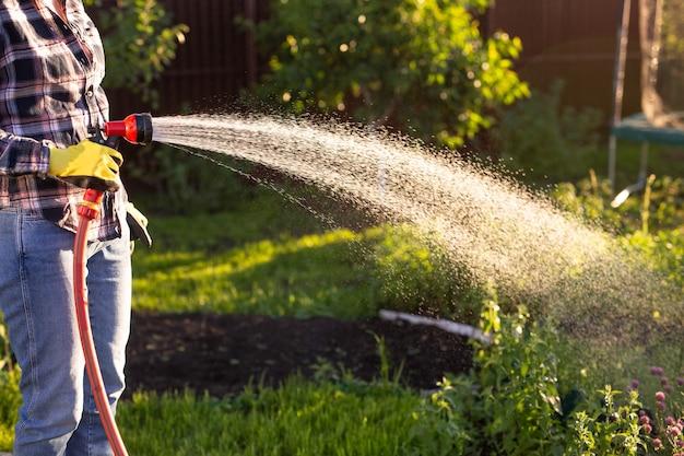 Mani femminili che tengono il tubo dell'acqua da giardino indossando stivali colorati che irrigano il giardino