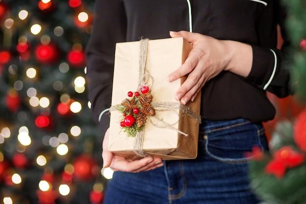 Mani femminili che tengono confezione regalo. natale, anno nuovo, concetto di compleanno. sfondo festivo con bokeh e luce solare. fiaba magica