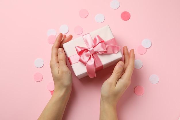 Mani femminili che tengono confezione regalo su sfondo rosa