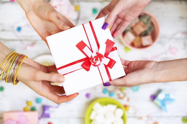 Mani femminili che tengono il primo piano del regalo