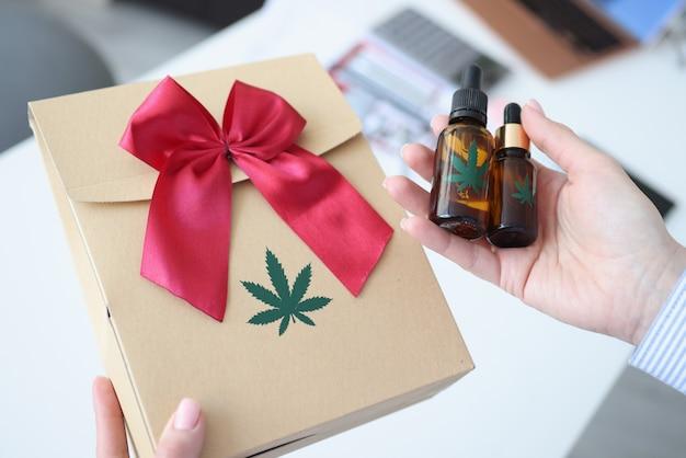 Mani femminili che tengono la carta da regalo con il primo piano di marijuana. vendita legale del concetto di marijuana
