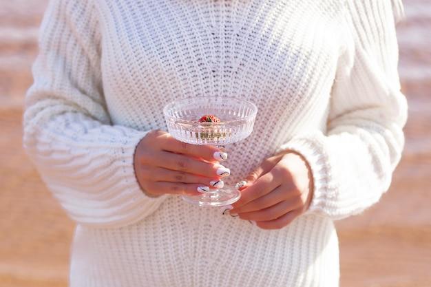 Mani femminili che tengono bicchiere d'acqua con fragole con mare sullo sfondo di sabbia