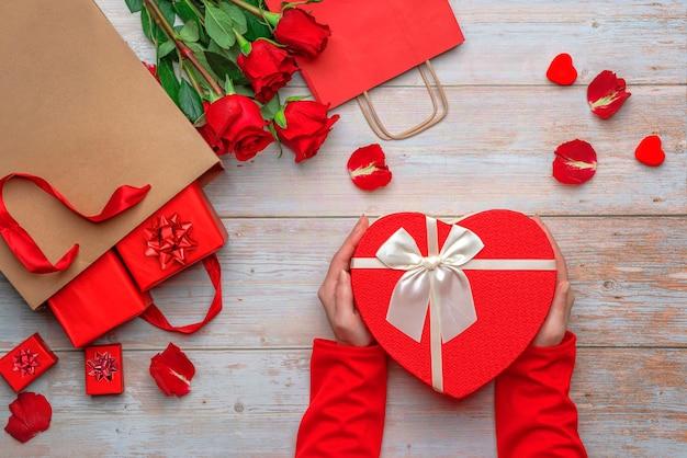 Mani femminili che tengono i regali degli amanti delle scatole a forma di cuore su una superficie di legno rose