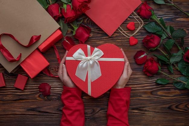 Mani femminili che tengono i regali degli amanti delle scatole a forma di cuore su una superficie di legno