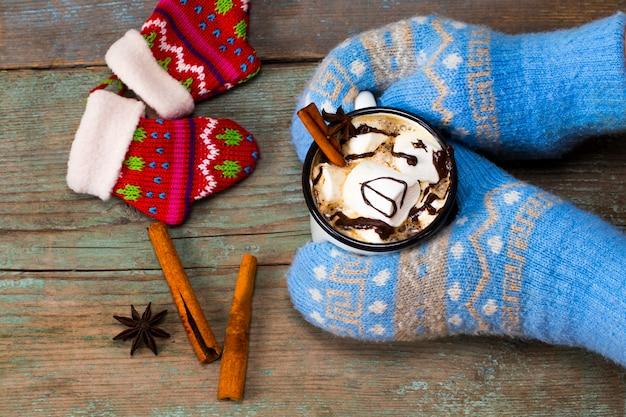 Mani femminili che tengono cioccolata calda con marshmallow.