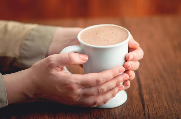 Mani femminili che tengono tazza calda di cacao sulla scrivania in legno. focalizzazione morbida