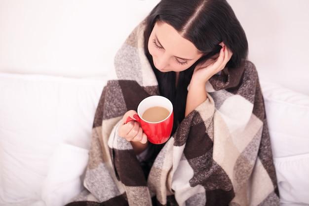 Mani femminili che tengono le bevande calde al cioccolato inverno e concetto di natale giovane donna felice