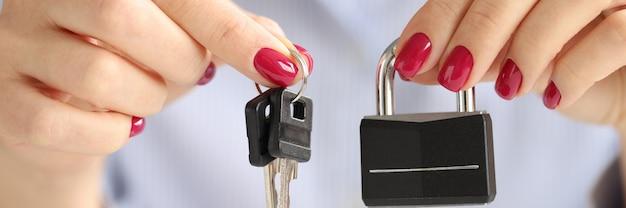 Mani femminili che tengono il primo piano di serratura e chiavi di ferro. concetto di sicurezza domestica