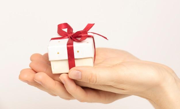 Mani femminili che tengono una piccola confezione regalo di lusso. isolato su sfondo bianco. natale e capodanno. modello di mock up pronto per il tuo design.