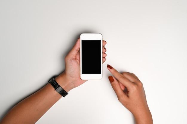 Mani femminili che tengono finto smartphone con schermo vuoto.