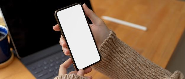 Mani femminili che tengono derisione sullo smartphone mentre sedendosi nell'area di lavoro con la compressa digitale sulla tavola di legno