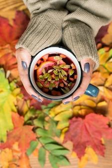 Mani femminili che tengono tazza di tisana calda con limone su foglie autunnali multicolori