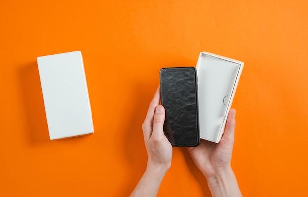 Mani femminili che tengono nuovo smartphone nella casella. unboxing vista dall'alto su sfondo arancione, minimalismo