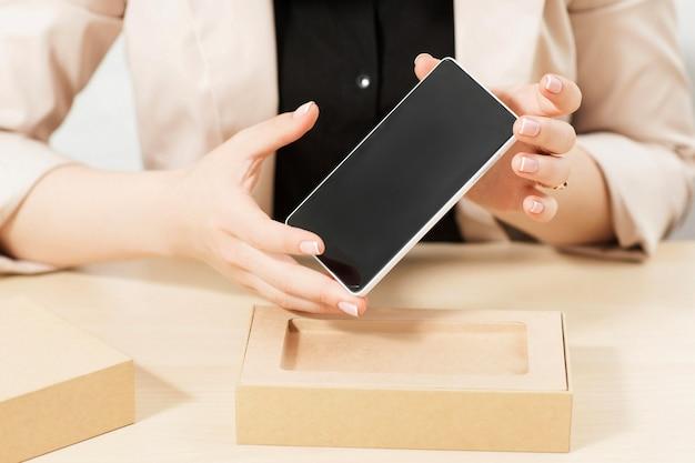 Mani femminili che tengono nuovo smartphone