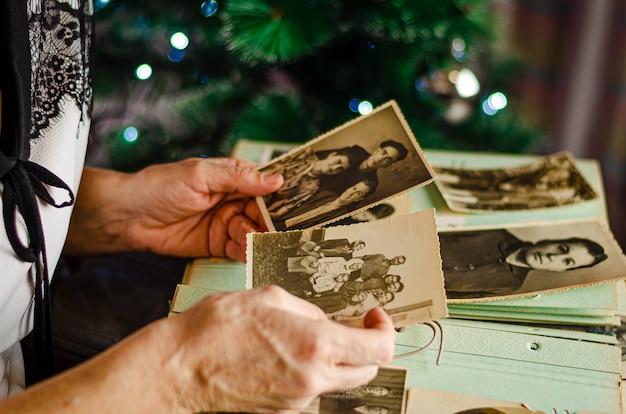 Mani femminili che tengono e vecchia foto dei suoi parenti