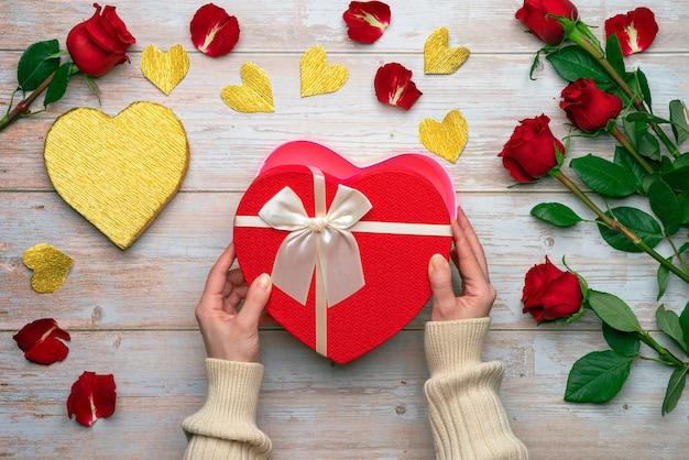 Mani femminili che tengono scatole a forma di cuore aperte amanti regali su superfici in legno petali di rose