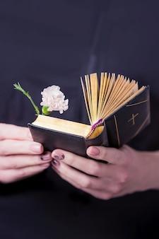 Mani femminili che tengono aperto libro di preghiere vintage e fiore di garofano rosa su una parete nera
