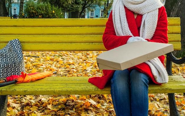 Mani femminili che tengono la scatola del pacchetto con pizza. consegna del concetto e take away durante una pandemia