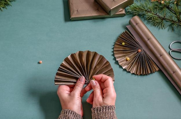 Mani femminili che tengono ventaglio di carta e tallone sopra il tavolo. decorazioni per la casa, regali di imballaggio per la cura. concetto fai da te.