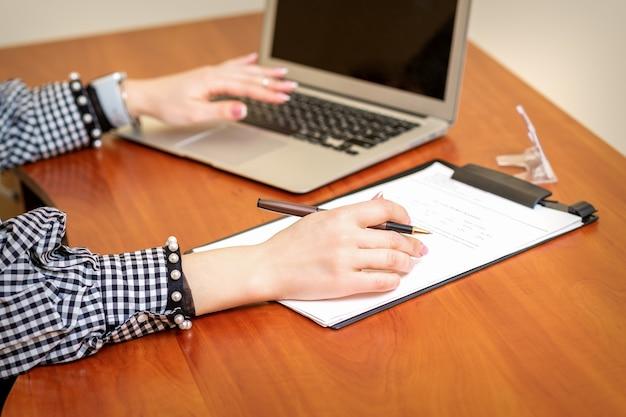 Mani femminili che tengono la penna sotto il documento e lavorano con il computer portatile al tavolo in un ufficio