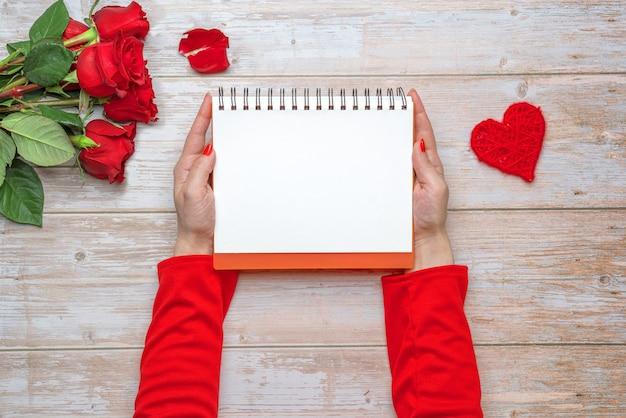 Mani femminili che tengono una scatola regalo a forma di cuore di quaderno con copertina rigida con rose in raso