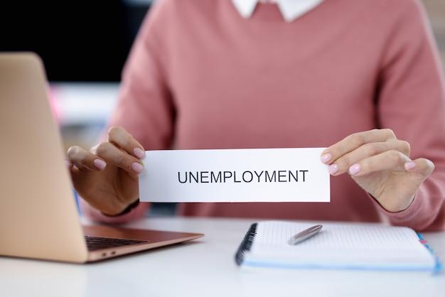 Mani femminili che tengono pezzo di carta con il primo piano di disoccupazione di parola. difficoltà con il concetto di lavoro