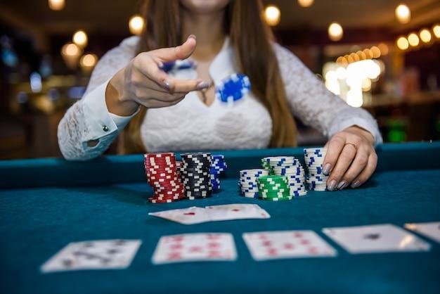 Mani femminili che tengono pile di fiches del casinò sul tavolo