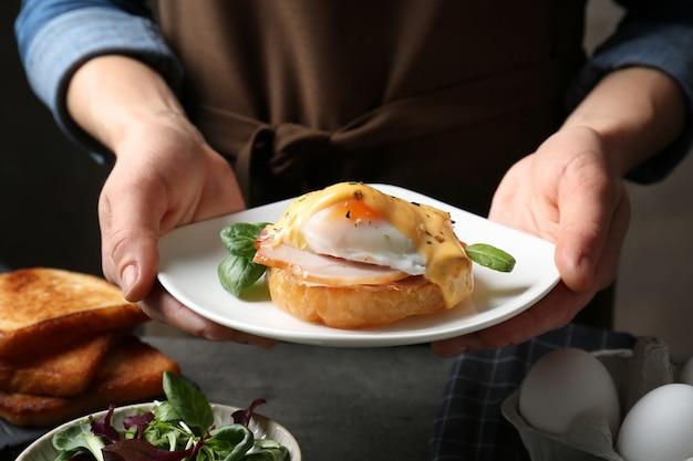 Mani femminili che tengono piatto con gustoso uovo