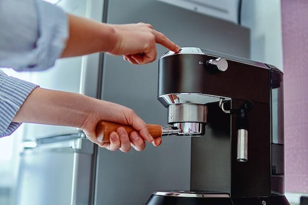 Mani femminili che tengono il portafiltro e fanno il caffè aromatico fresco a casa utilizzando una moderna macchina per il caffè