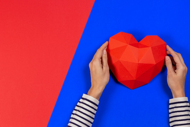 Mani femminili che tengono cuore poligonale rosso su sfondo blu e rosso. vista dall'alto