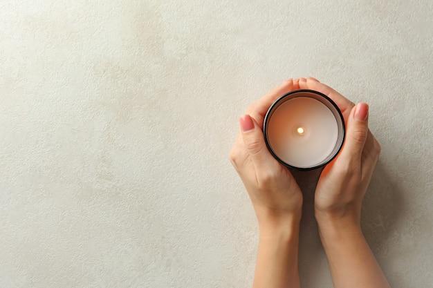 Mani femminili che tengono candela profumata, vista dall'alto