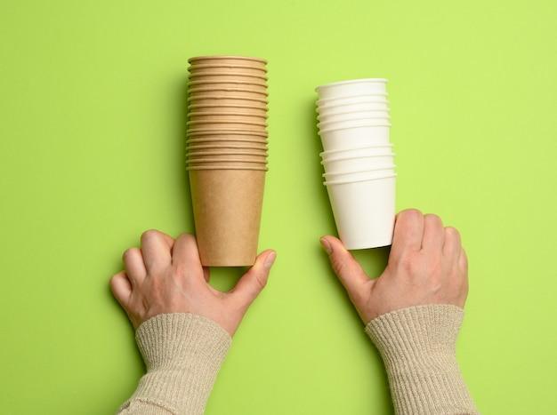 Mani femminili che tengono una pila di tazze usa e getta di carta marrone e bianca, da vicino