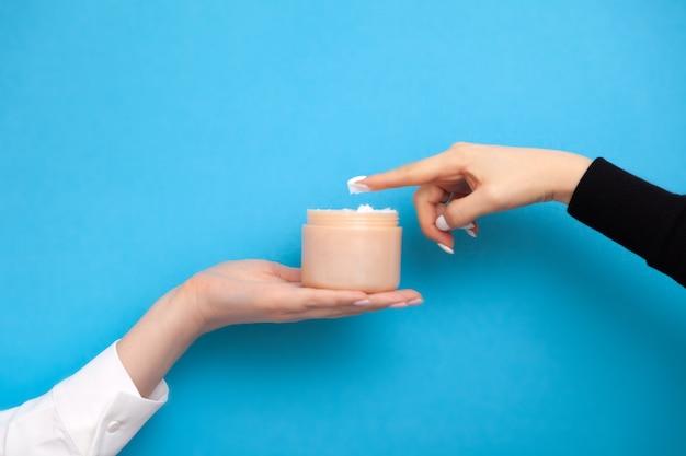 Mani femminili che tengono e provano la crema dal barattolo