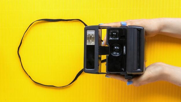 Mani femminili che tengono fotocamera foto d'epoca su sfondo giallo
