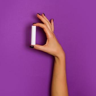 Mani femminili che tengono bottiglia cosmetica bianca su fondo viola