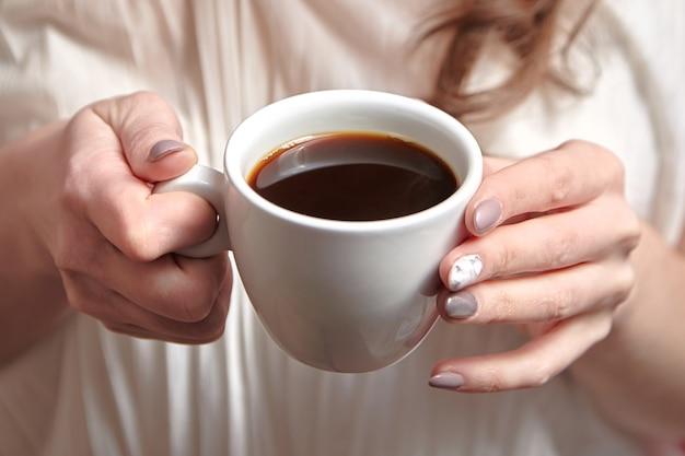 Mani femminili che tengono tazza bianca di caffè nero