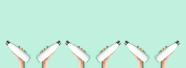 Mani femminili che tengono bottiglie termiche in acciaio riutilizzabili eco bianche