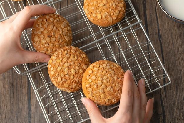 Mani femminili che tengono i biscotti integrali sulla tavola di legno