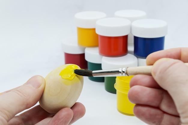 Mani femminili che tengono uovo di pasqua in legno e dipingerlo con vernice gialla