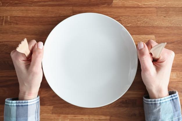 Mani femminili che tengono forchetta e coltello di legno vicino al primo piano bianco del piatto