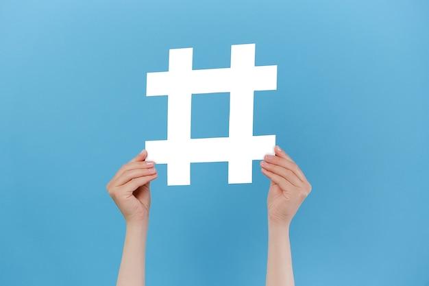 Le mani femminili tengono in mano un grande cartello hashtag bianco
