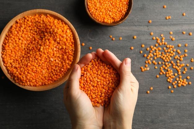 Le mani femminili tengono i legumi rossi sopra un buio con ciotole di legumi